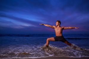 Man in yoga warrior pose on ocean beach at dusk