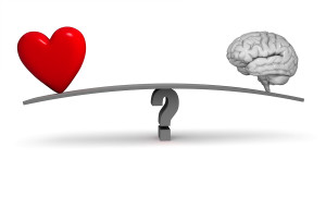 A bright red heart and gray brain sit on opposite ends of a dark gray board balanced on a gray question mark. Isolated on white.